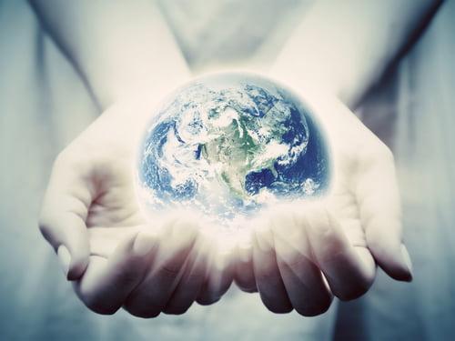 La terre brille dans les mains de la jeune femme.  Concepts de sauver le monde, protection, prendre soin, environnement.