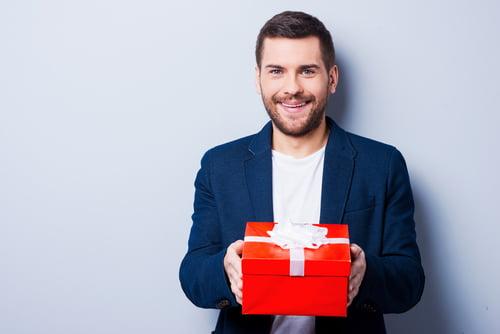Ce cadeau est pour toi.  Beau jeune homme en tenue de soirée vous offrant un cadeau en se tenant debout sur fond gris